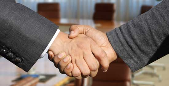 Close up on the hands of two men in business suite shaking hands.  Both have clean hands, and one of the hands has darker skin.